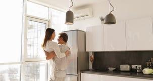 Hombre sonriente feliz Carry Asian Woman, par romántico joven junto en cocina metrajes