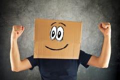 Hombre sonriente feliz con la caja de cartón en su cabeza y puño aumentado Fotos de archivo libres de regalías