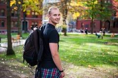 Hombre sonriente feliz del estudiante con la mochila que va a estudiar en campus universitario Fotos de archivo
