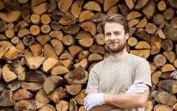 Hombre sonriente feliz delante de la leña tajada apilada Foto de archivo