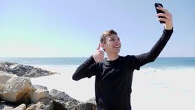 Hombre sonriente feliz joven que toma imágenes de sí mismo que ríe y que muestra los pulgares para arriba en una playa rocosa con almacen de video