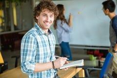 Hombre sonriente feliz que estudia con los estudiantes en sala de clase Fotos de archivo