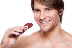 Hombre sonriente hermoso con la barra de chocolate Foto de archivo libre de regalías