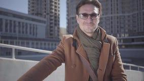 Hombre sonriente hermoso en gafas de sol y situación marrón de la capa con su bicicleta en la ciudad que mira en la cámara Ocio metrajes