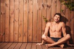Hombre sonriente hermoso joven en el traje de baño que se sienta con las piernas cruzadas Imagen de archivo