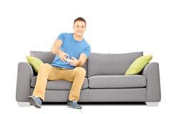 Hombre sonriente joven asentado en un sofá que juega a los videojuegos Fotos de archivo