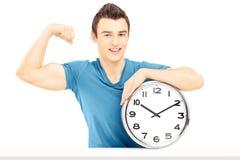 Hombre sonriente joven asentado en una tabla con el reloj de pared que muestra el suyo Imagen de archivo