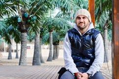 hombre sonriente joven barbudo que se sienta en la playa tropical con las palmeras Fotografía de archivo