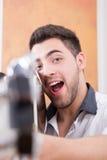 Hombre sonriente joven con la expresión que señala la guitarra en usted Imagen de archivo