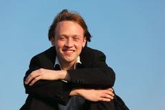 Hombre sonriente joven contra el cielo Foto de archivo