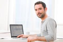 Hombre sonriente joven delante de un ordenador Fotos de archivo