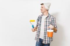 Hombre sonriente joven en el sombrero del periódico que sostiene el rodillo de pintura para la pintura de pared y el cubo vacío d imagen de archivo libre de regalías