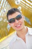 Hombre sonriente joven en gafas de sol Fotografía de archivo libre de regalías
