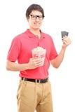 Hombre sonriente joven que celebra una caja de las palomitas y dos boletos para el cine Imagen de archivo libre de regalías