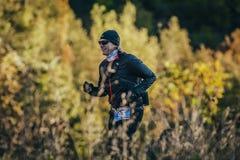 Hombre sonriente joven que corre en bosque del otoño Fotografía de archivo