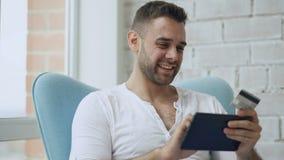 Hombre sonriente joven que hace compras en línea usando la tableta digital que se sienta en el balcón en casa metrajes