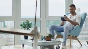 Hombre sonriente joven que hace compras en línea usando la tableta digital que se sienta en el balcón en el apartamento moderno d almacen de metraje de vídeo