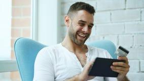 Hombre sonriente joven que hace compras en línea usando la tableta digital que se sienta en el balcón en casa fotos de archivo