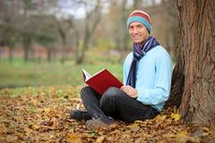 Hombre sonriente joven que lee un libro en el parque de la ciudad Imágenes de archivo libres de regalías
