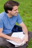 Hombre sonriente joven que parece ausente mientras que trabaja en la hierba Fotos de archivo libres de regalías