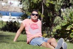 Hombre sonriente joven que pone en un prado verde con una opinión del mar Silla de cubierta en la playa en Brighton Foto de archivo libre de regalías