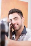 Hombre sonriente joven que señala la guitarra en usted Imagen de archivo