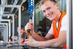 Hombre sonriente joven que trabaja en la cadena de producción imagen de archivo libre de regalías