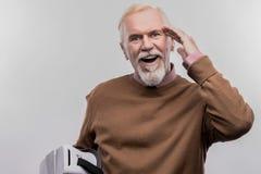 Hombre sonriente jubilado que lleva el suéter marrón que siente excitado extremadamente imagen de archivo