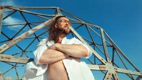 Hombre sonriente masculino con la situación desnuda del torso con la mano cruzada que presenta en el fondo de la rejilla del ciel almacen de metraje de vídeo