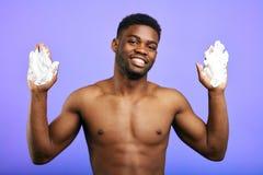 Hombre sonriente positivo que muestra sus manos en crema fotografía de archivo libre de regalías