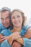 Hombre sonriente que abraza a su esposa de detrás Imagen de archivo