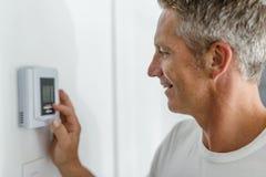 Hombre sonriente que ajusta el termóstato en sistema de la calefacción de casa foto de archivo