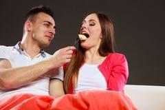 Hombre sonriente que alimenta a la mujer feliz con el plátano Imagenes de archivo