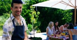 Hombre sonriente que asa a la parrilla maíz, la carne y la verdura en barbacoa metrajes
