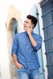 Hombre sonriente que camina y que escucha el teléfono móvil Fotografía de archivo libre de regalías