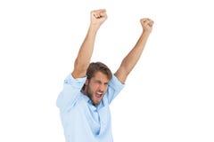 Hombre sonriente que celebra éxito con los brazos para arriba Fotografía de archivo