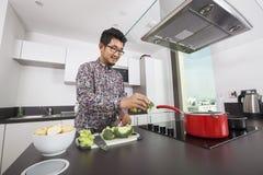 Hombre sonriente que cocina en cocina en casa Imagen de archivo libre de regalías