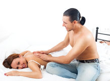 Hombre sonriente que da masajes al detrás de su mujer Fotografía de archivo libre de regalías