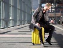 Hombre sonriente que descansa en el aeropuerto con el teléfono móvil Imagenes de archivo