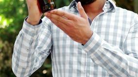 Hombre sonriente que examina una botella de vino almacen de metraje de vídeo