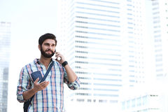 Hombre sonriente que gesticula mientras que usa el teléfono celular en ciudad Foto de archivo libre de regalías