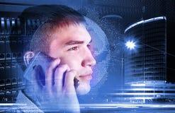 Hombre sonriente que habla en el teléfono delante de un mapa del mundo 3d, de rascacielos y de servidores Imagen de archivo libre de regalías