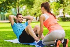 Hombre sonriente que hace ejercicios en la estera al aire libre Imagenes de archivo