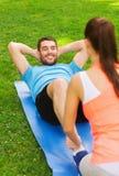 Hombre sonriente que hace ejercicios en la estera al aire libre Foto de archivo libre de regalías