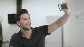 Hombre sonriente que hace el selfie en el teléfono en la cocina abierta Teléfono joven de la tenencia del individuo metrajes
