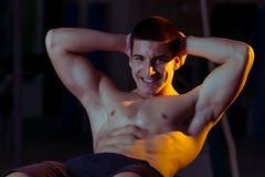 Hombre sonriente que hace Excerise abdominal Fotos de archivo