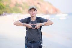 Hombre sonriente que hace forma del corazón con sus manos la playa Fotos de archivo