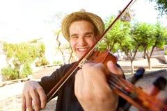Hombre sonriente que juega una canción en el violín Fotos de archivo libres de regalías