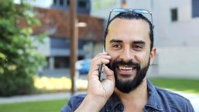 Hombre sonriente que llama por smartphone en la calle 22 de la ciudad metrajes