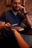 Hombre sonriente que lleva a cabo hacia fuera su célula Fotografía de archivo libre de regalías